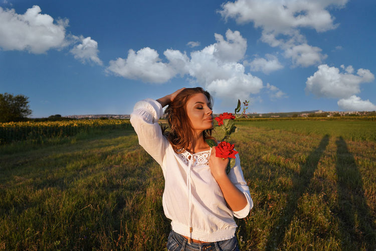 Young woman holding flower standing on field against sky
