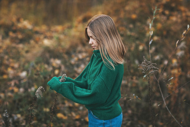 Portrait of a beautiful teenage girl with blond hair and blue eyes in an autumn park.