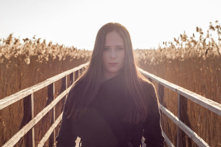 Portrait of young woman standing on boardwalk at farm during sunset