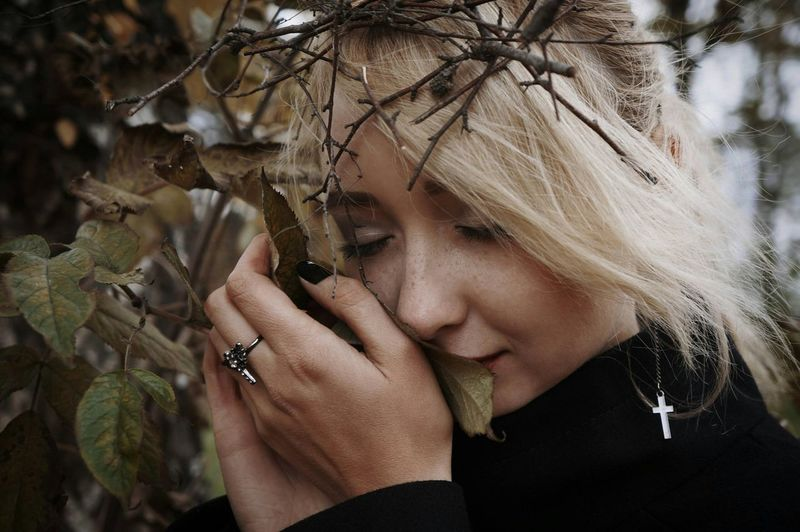 Close-up of beautiful young woman with eyes closed holding branches