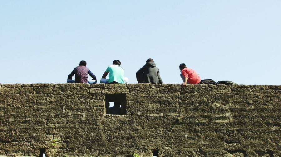 Rear View Of Friends Sitting On Surrounding Wall Against Sky