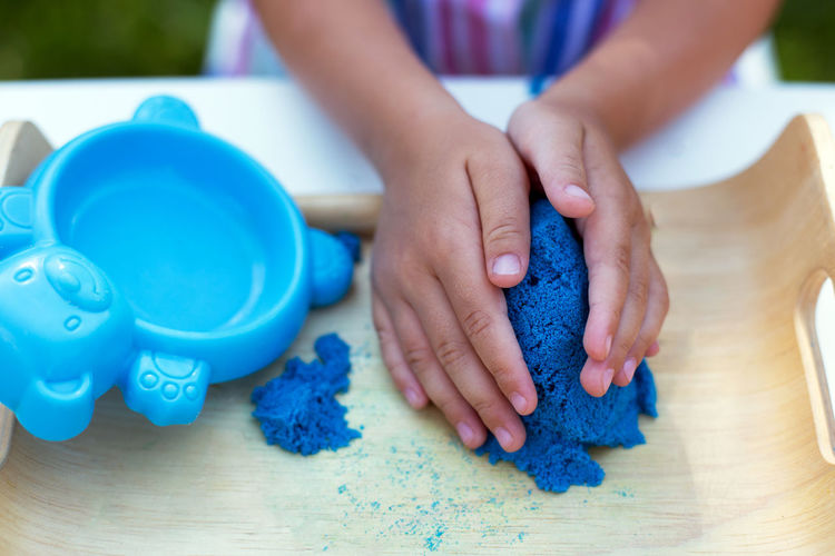Close-up of hands on blue table