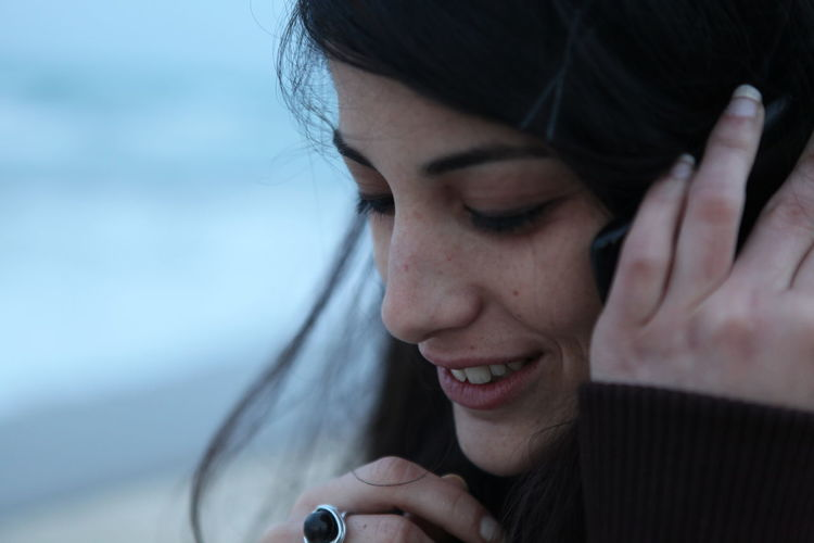 Close-up of smiling woman talking on phone at beach
