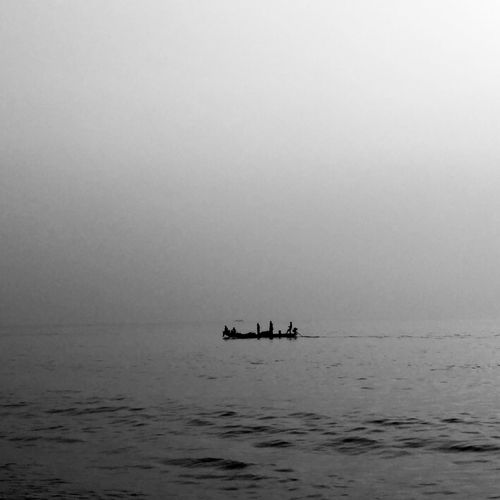Silhouette people on boat sailing in sea against clear sky