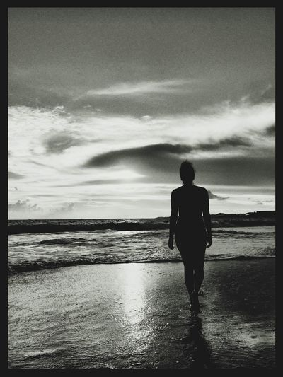 Rear view of silhouette man standing at beach