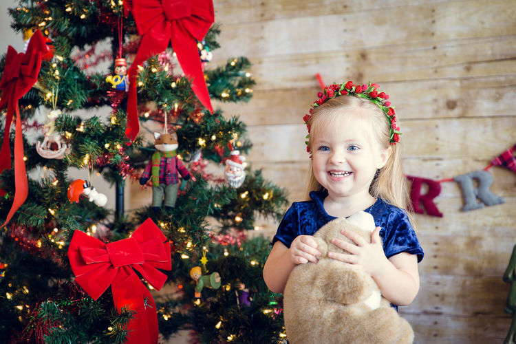 Cute girl holding teddy bear standing by decorated christmas tree against wall at home