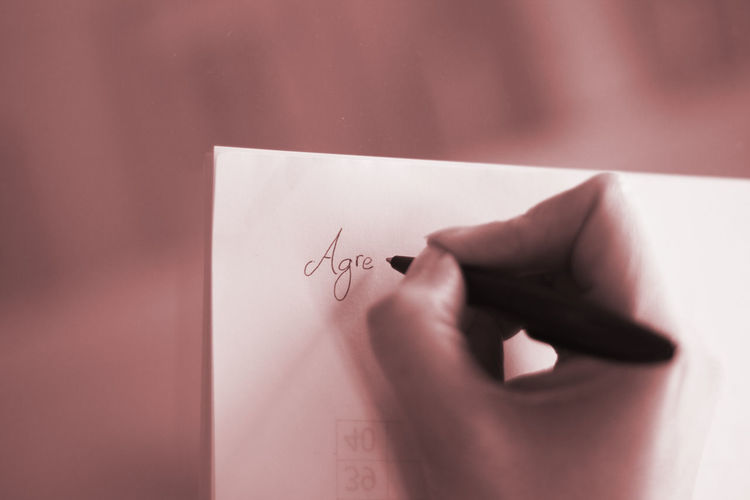Close-up of hand holding paper with text