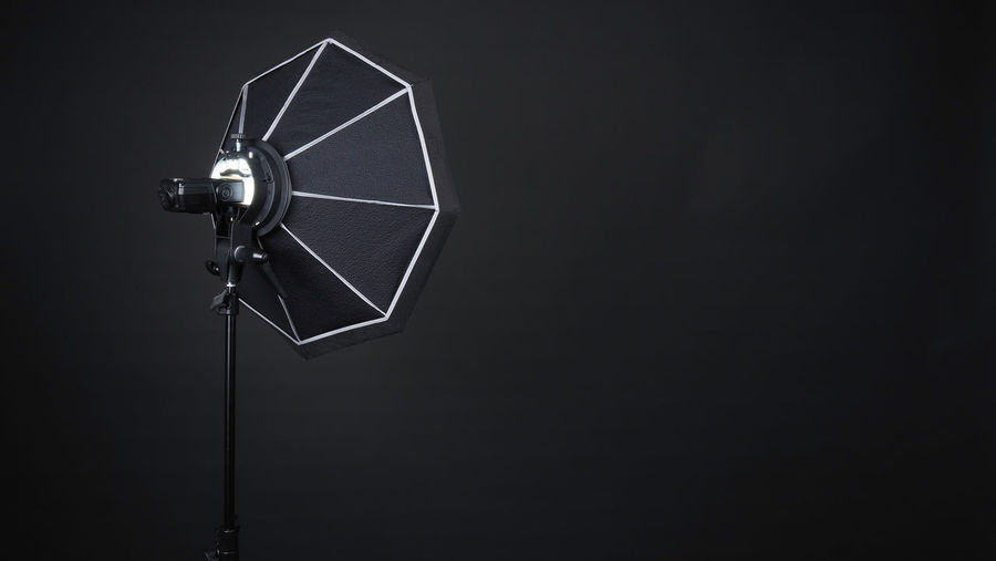 Professional photo studio soft box and flash on the tripod for stillphoto or video production which ready for shape the light for softer, harder or sharper by crew team before shooting on black background. Technology Studio Shot Indoors  Arts Culture And Entertainment Equipment Black Background Retro Styled Copy Space Lighting Equipment Single Object Black Color Photography Themes Music No People Cut Out Close-up Alternative Energy Man Made Illuminated Electric Lamp Electrical Equipment Behind The Scenes Studio; Soft; Box; Photo; Photography; Light; Flash; Equipment; Isolated; Background; Black; Camera; White; Spotlight; Stand; Tripod; Professional; Lamp; Photograph; Lights; Photographer; Technology; Soft-box; Flashlight; Halogen; Tool; Electric; Strobe;