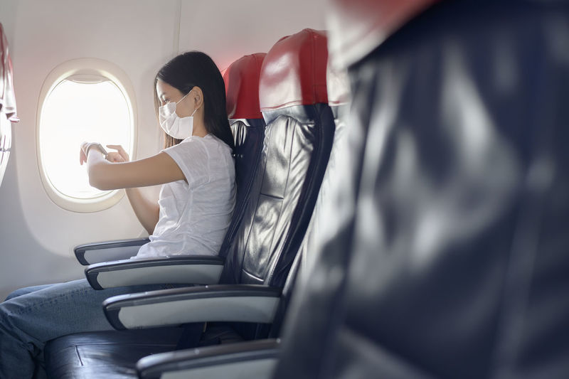 Close-up woman wearing mask using smart watch in airplane