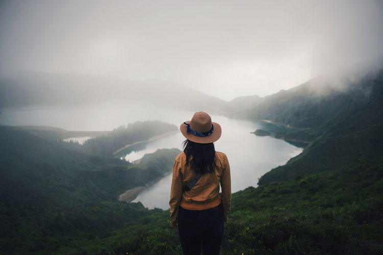 Woman standing on mountain during foggy weather