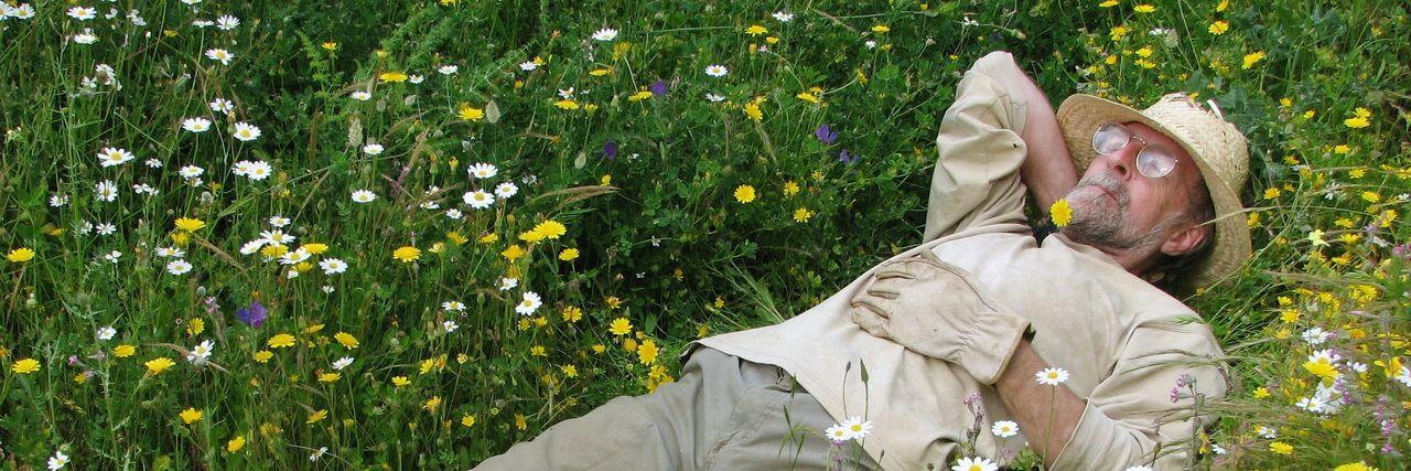 Senior man relaxing in grass