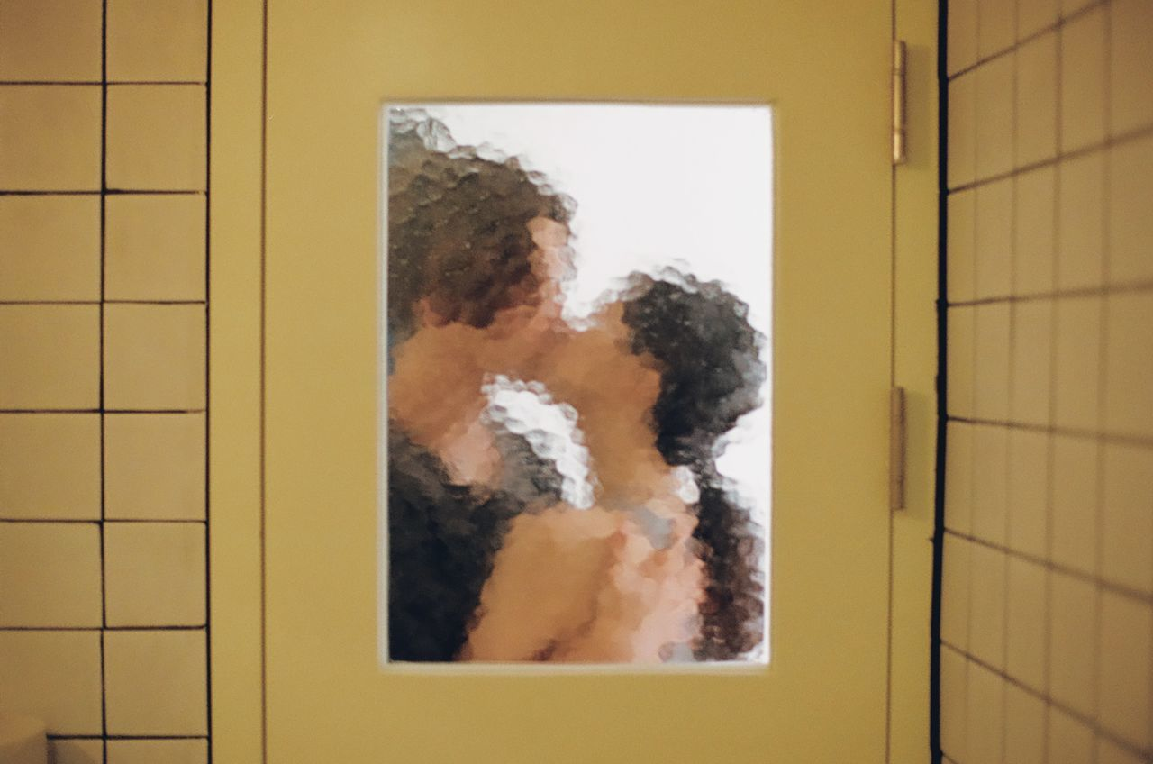 Couple kissing on the mouth seen through glass door
