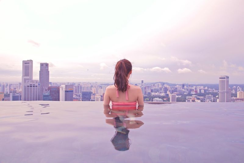Rear View Of Woman Standing In Infinity Pool Against Buildings In City