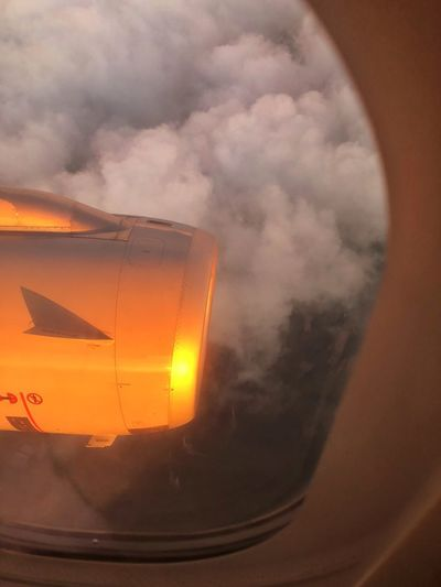 Close-up of airplane window against sky during sunset
