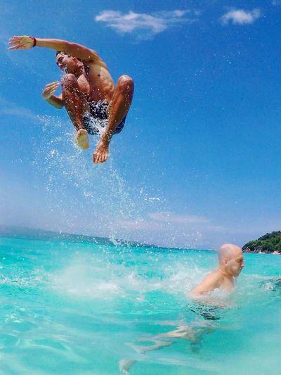Full length of shirtless man jumping in swimming pool