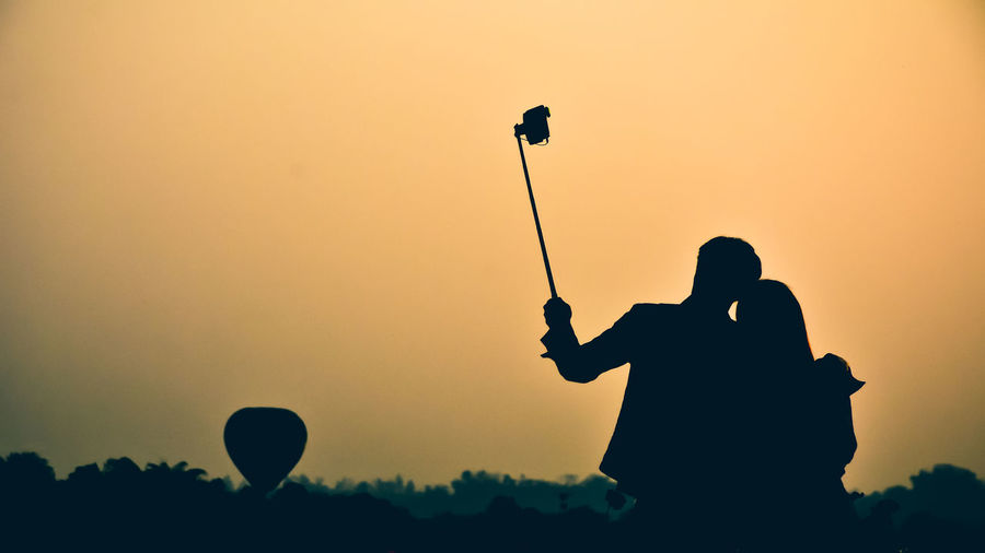 Silhouette couple taking selfie against clear sky during sunset