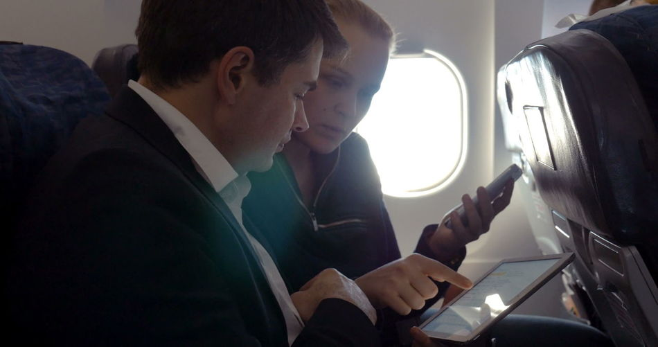 Midsection of man using mobile phone while sitting in airplane
