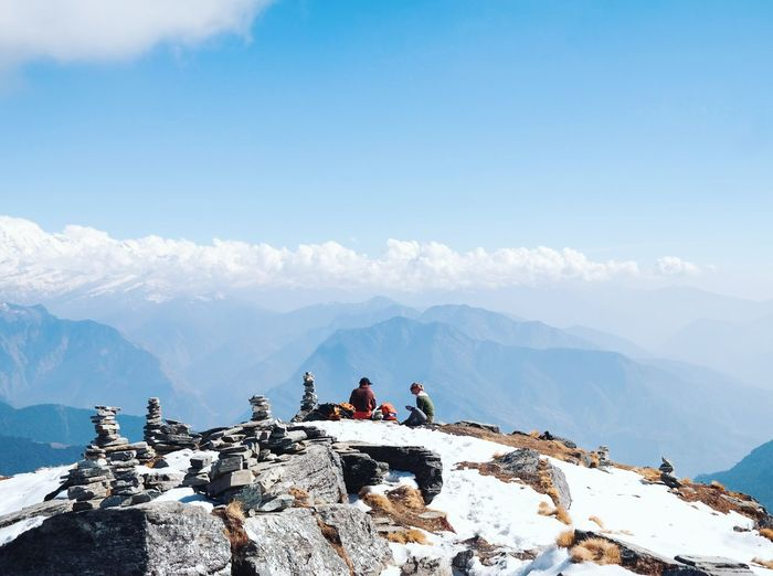 Friends sitting on snowcapped mountain peak against cloudy sky