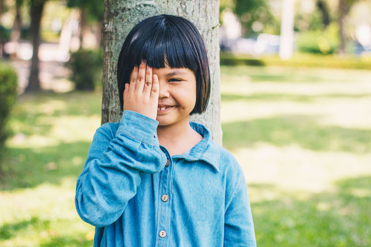 Portrait of smiling girl with hand covering eye against tree trunk