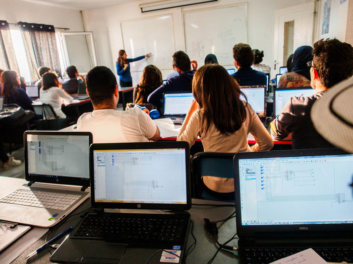 Engineering students in the classroom with their laptops. Professor Students Classroom Computer Computer Engineering Computer Equipment Crowd Education Group Group Of People Indoors  Information Technology Laptop Men Sitting Table Teacher Technology Using Laptop Whiteboard Women