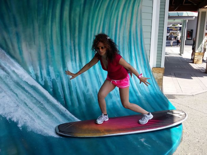 Optical Illusion Of Woman With Arms Outstretched Surfboarding