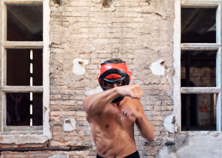 Portrait of young man punching while standing against wall