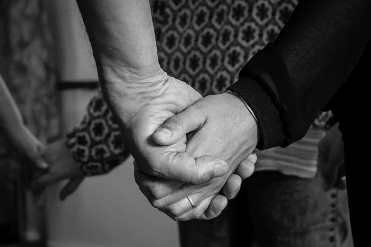 Midsection of people holding hands