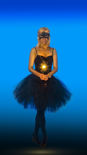 Portrait Of Female Ballet Dancer Holding Sparkler Standing Against Blue Background