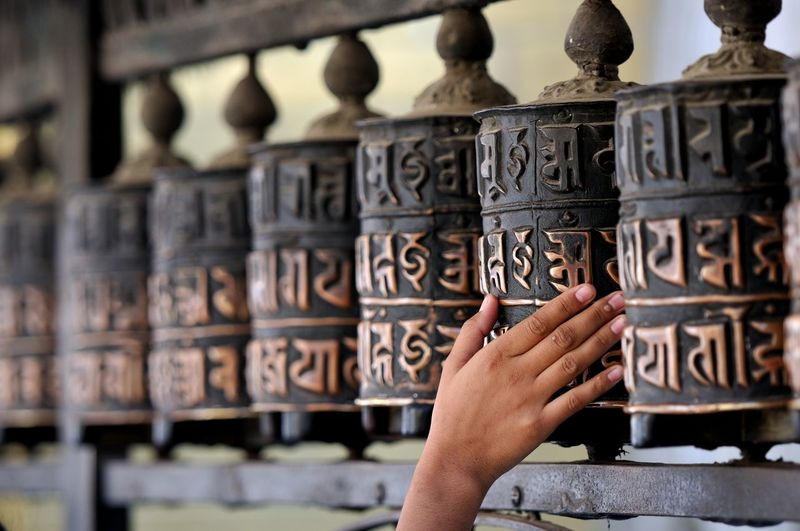 Cropped Image Of Person Touching Prayer Wheel