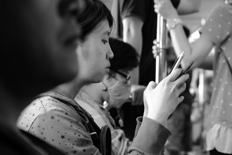 Young woman using mobile phone while traveling in train
