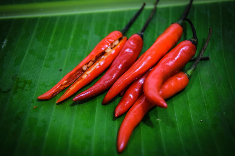 Close-Up Of Red Chili Peppers On Leaf