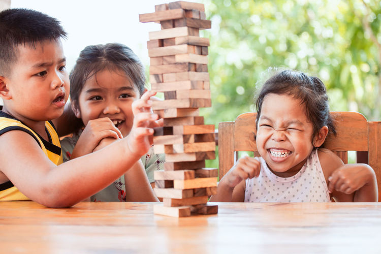 Sisters Playing With Wooden Toy Blocks On Table While Sitting In Porch