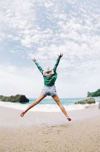 Arms Raised Beach Cloud - Sky Day Emotion Enjoyment Excitement Freedom Full Length Fun Happiness Human Arm Jumping Land Leisure Activity Limb Mid-air Nature One Person Outdoors Positive Emotion Sea Sky Water