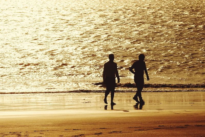 Silhouette of men walking at beach during sunset