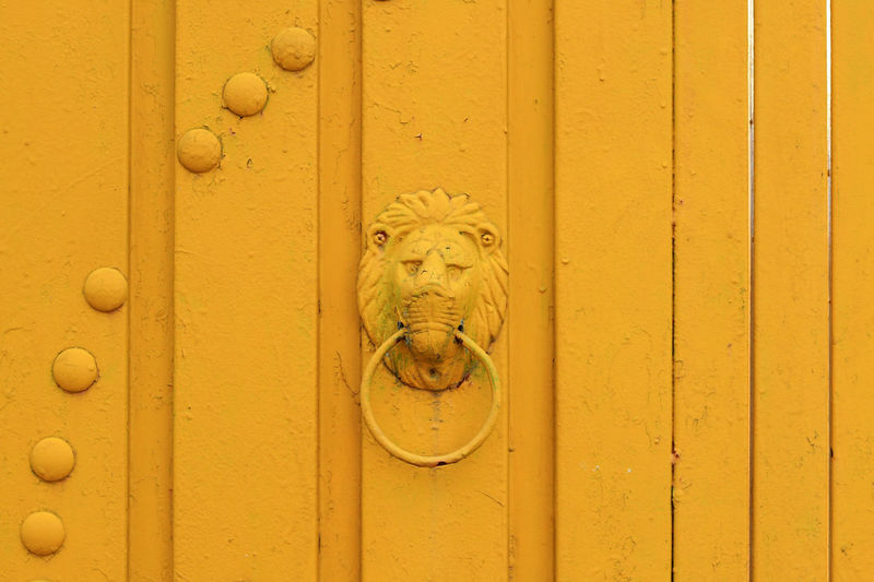 Close-up of knocker on yellow door