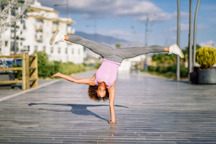 Young Woman Exercising Handstand At Footpath