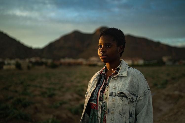 Portrait of teenage girl standing on land against sky