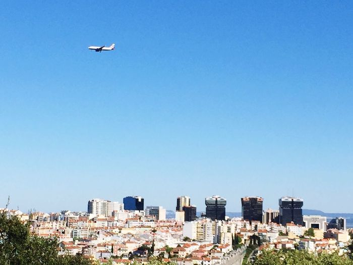 Airplane Over Town Against Clear Blue Sky
