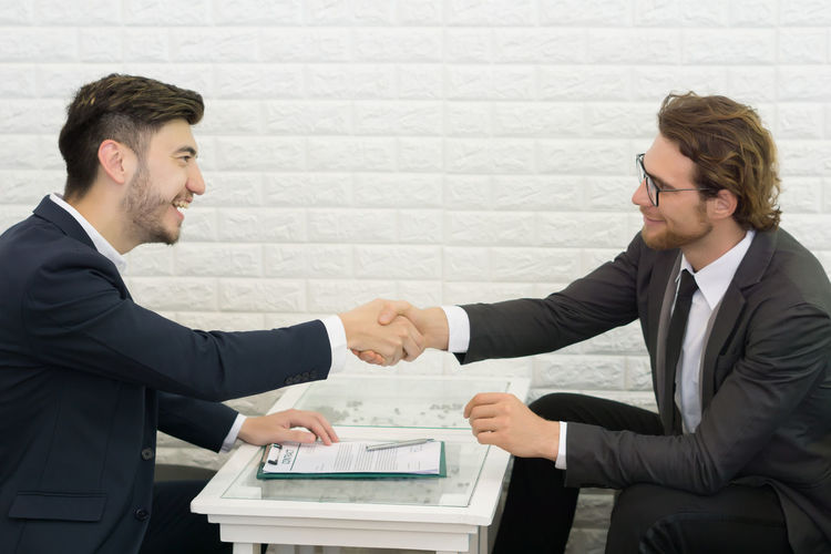 Businessmen shaking hands while sitting at table in office
