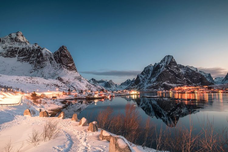 Fishing village illuminated in mountain valley reflection on winter at dawn. Reine, Lofoten islands, Norway Beauty In Nature Scenics - Nature Water Sky Mountain Cold Temperature Lake Snow Winter Tranquility Tranquil Scene Nature Reflection Mountain Range Non-urban Scene Snowcapped Mountain Idyllic Environment No People Lofoten Norway Scandinavia Winter