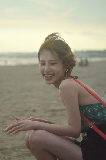 Portrait of a smiling young woman sitting on beach