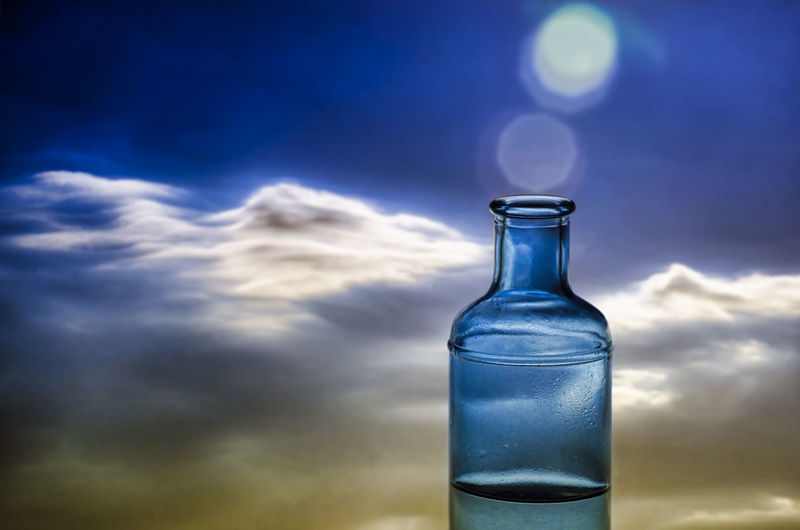 Close-up of glass bottle against blue sky