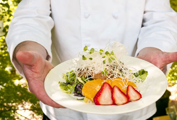 Chef holding food Midsection Food And Drink One Person Food Healthy Eating Holding Focus On Foreground Fruit Standing Hand Chef Front View Garnish Chicken Meat Strawberries Oranges