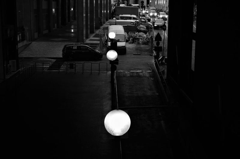 Illuminated Street Lights On Road By Buildings At Night
