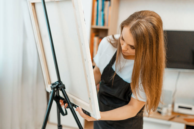 Woman adjusting canvas on easel at home