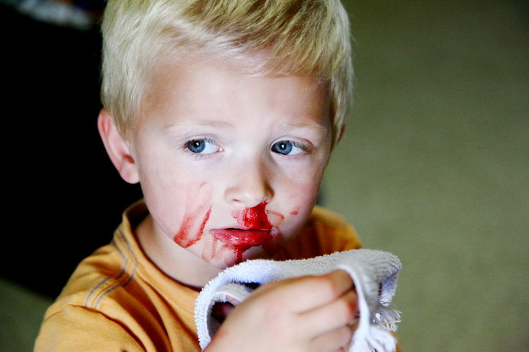 Close-up of sad boy with blood on nose