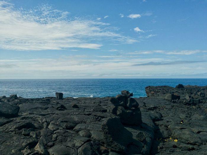 Man sitting on rocks by sea against sky