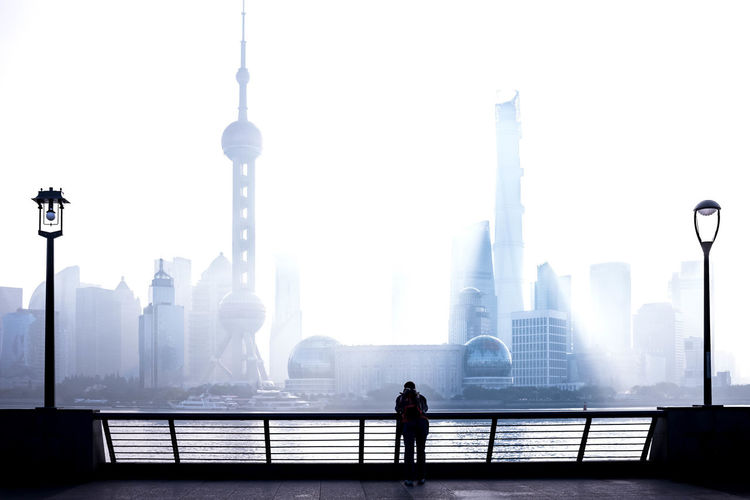 Man standing on railing against buildings in city