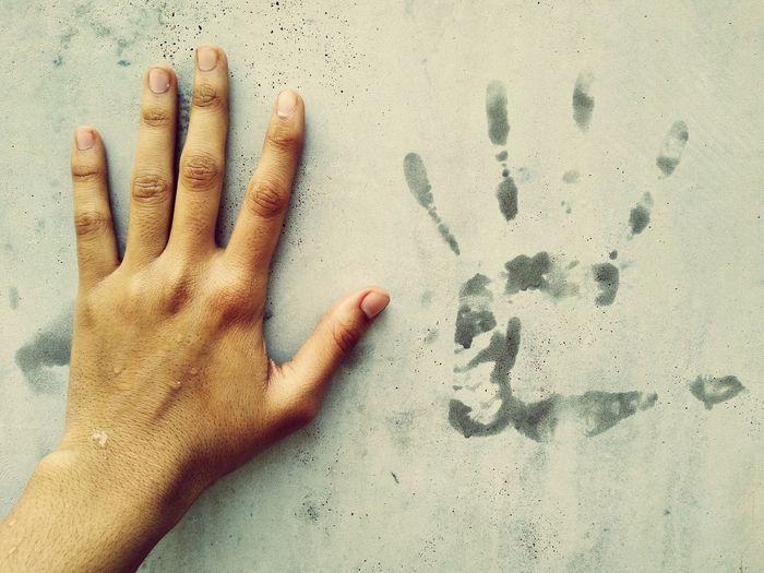 High angle view of human hand on sand