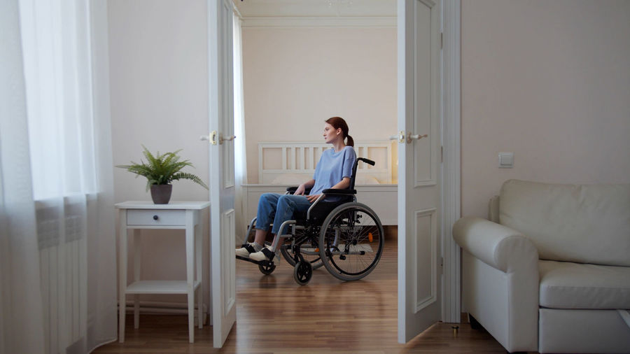 Full length of woman sitting on door at home